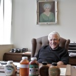 Gene Biggi at his desk, his mother's portrait behind him.